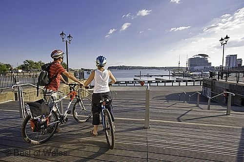 A couple on bikes stare out over Cardiff Bay